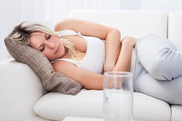 Portrait of woman with stomach ache sitting sofa